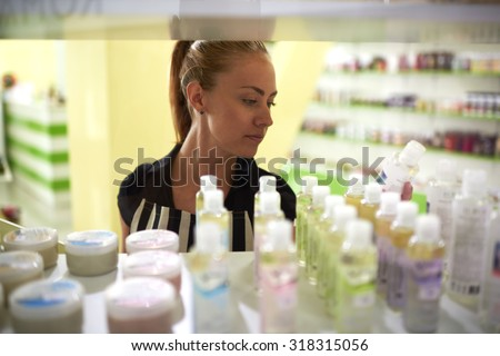 Young attractive woman consultant lays out beauty on store shelves, attractive female reads the contents of the product before making a purchase in cosmetic shops, buyer consider aromatic fluids - stock photo