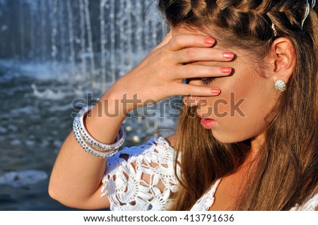 young attractive woman cooling near the fountain in hot weather - stock photo