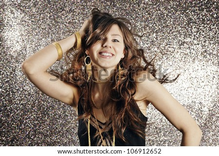 Young attractive woman dancing against a silver glitter background in a night club. - stock photo