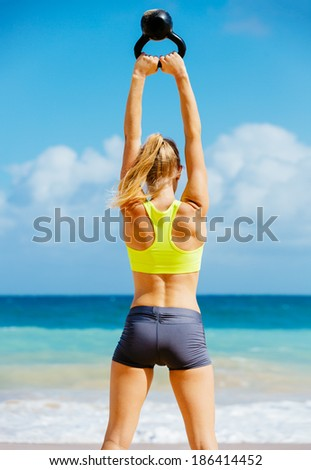 Young attractive woman doing kettle bell exercises outside. Fitness woman working out at the beach.  Fitness Concept. - stock photo