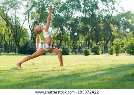 young attractive woman doing yoga in the park, active lifestyle