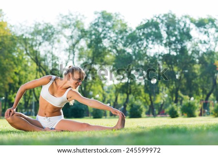 young attractive woman doing yoga in the park, active lifestyle - stock photo