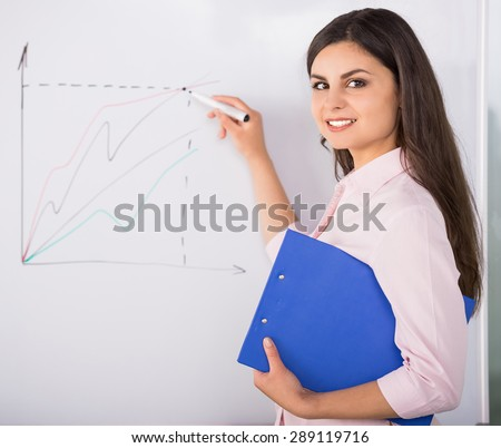 Young attractive woman drawing business strategy on flip chart.