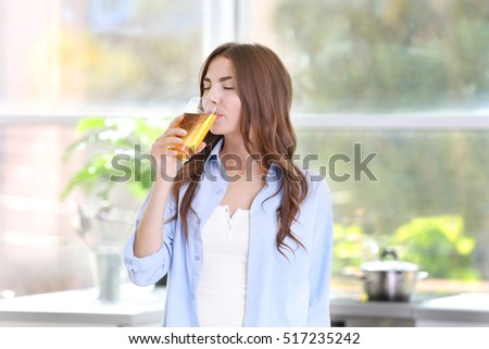 Young attractive woman drinking apple juice