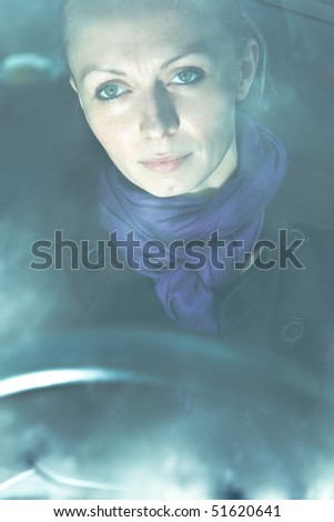 Young attractive woman driving a car - shot through window