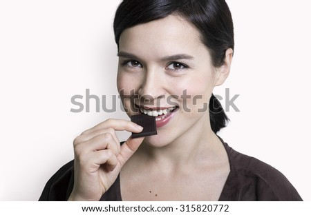 young attractive woman eating bitter chocolate - stock photo