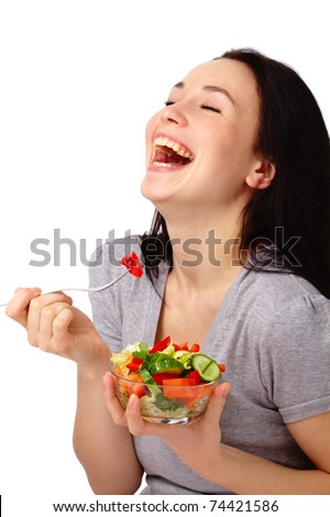 Young attractive woman eats vegetable salad using fork, isolated over white - stock photo