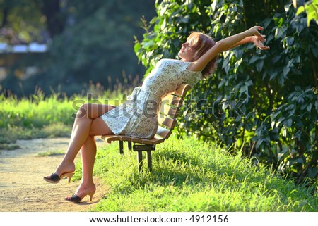 young attractive woman enjoying the sun in the park - stock photo