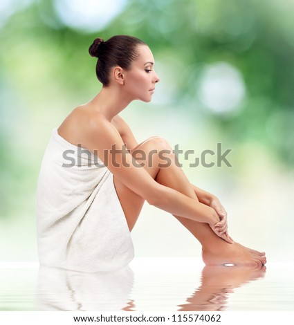 Young attractive woman getting spa on green background - stock photo