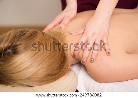Young attractive woman having her back massaged - stock photo