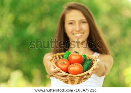 Young attractive woman holding basket of tomatoes and cucumbers, against green of summer park.