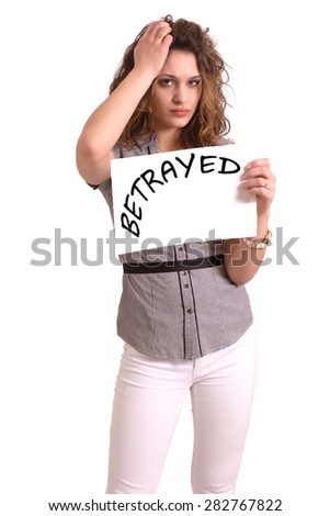 Young attractive woman holding paper with Betrayed text on white background - stock photo
