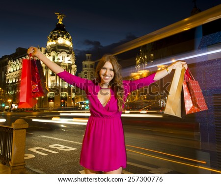 young attractive woman holding shopping bags in both hands posing at night in Madrid city after a shopping day in town wearing glamour dress in female fashion  - stock photo