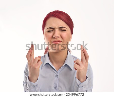 young attractive woman holds his fingers crossed and eyes closed, wishful thinking - stock photo