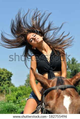 young attractive  woman  horseback riding  in summer day - stock photo
