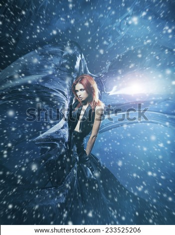 Young attractive woman in a blowing silk. Snowy background with wind, lighting and blizzard. - stock photo