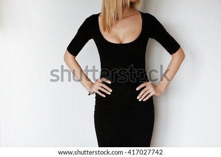 Young attractive woman in black low dress getting ready for first date. Cropped portrait of sensual blonde female holding arms on hips while trying on new cocktail dress she bought for the party  - stock photo