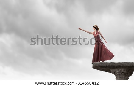 Young attractive woman in dress and blindfold on eyes - stock photo