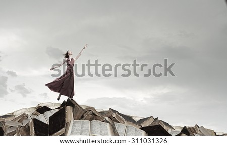 Young attractive woman in dress reaching hand to touch something - stock photo