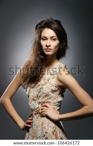 Young attractive woman in fashion dress over grey background
