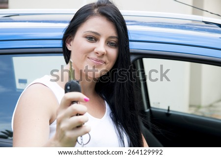Young Attractive woman in her car, smiling holding her keys - stock photo