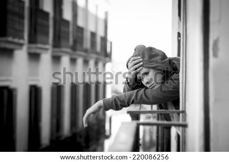 young attractive woman in hood shirt suffering depression and stress outdoors at home balcony terrace window in pain and grief feeling sad and desperate in urban background in black and white - stock photo