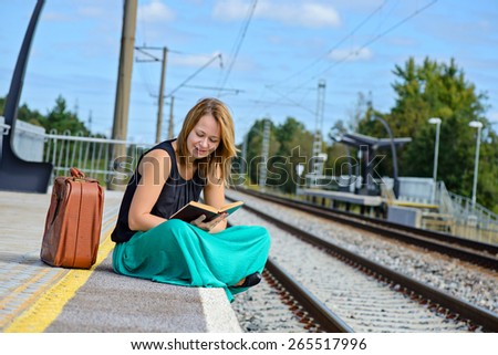 Young attractive woman in long skirt sitting on the train station and reading a book - stock photo