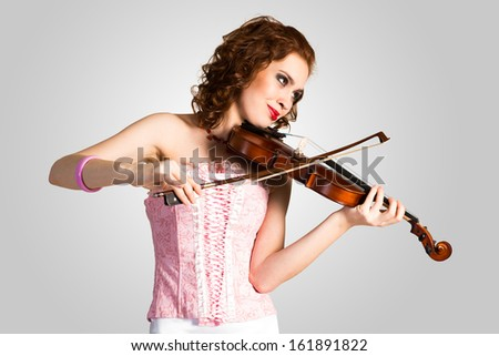 young attractive woman in pink corset playing the violin, enjoys music