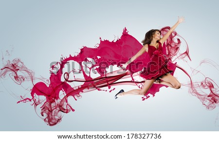 Young attractive woman in red dress jumping high - stock photo
