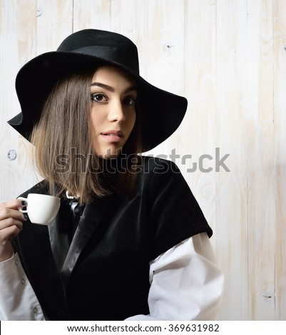 Young attractive woman in retro dress and hat drinking coffee over wooden background. Vintage stylization of lady with cup of coffee smelling delicate aroma of beverage. Image toned.  - stock photo
