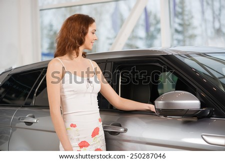 Young attractive woman in show room standing near car - stock photo