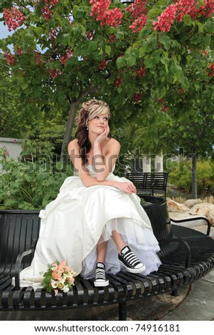 young attractive woman in sitting under colorful tree in a wedding dress - stock photo