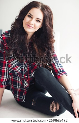 Young attractive woman in squared shirt posing in studio. Casual stile.  - stock photo