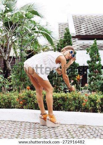Young attractive woman in white short dress and sunglasses rips off a beautiful flower in the street on a sunny day. Back view. Sexy buttocks. Tattoos on the legs. Outdoors lifestyle portrait