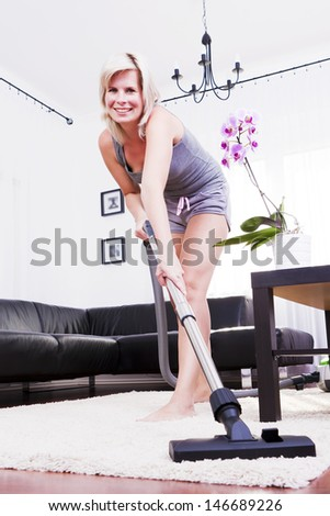 Young attractive woman is cleaning vacuum on carpet. - stock photo