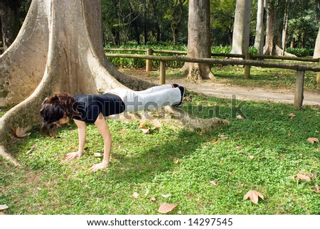 Young, attractive woman is performing a push-up next to a tree.   Horizontally framed shot - stock photo