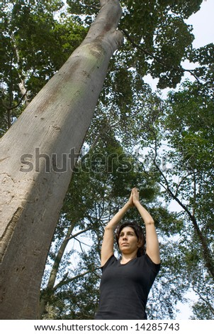 Young, attractive woman is standing next to a tree.   She appears to be performing yoga.  Vertically framed shot - stock photo