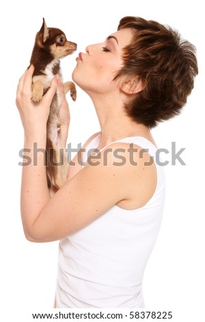 Young attractive woman kissing her puppy chihuahua, on white background - stock photo