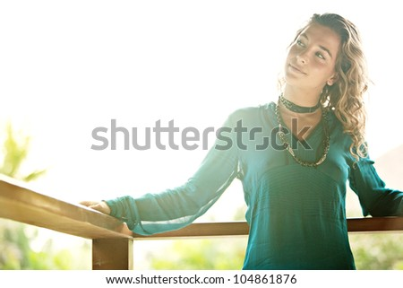 Young attractive woman leaning on a tropical garden balcony with the sun behind her, smiling.
