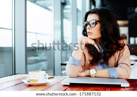 Young attractive woman looking away thoughtfully at her laptop - stock photo