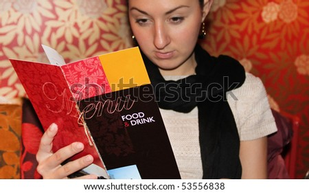 Young attractive woman looking in a menu in a restaurant  ( menue in focus ) - stock photo