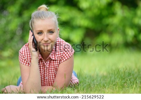 Young attractive woman lying on lawn with phone. MANY OTHER PHOTOS FROM THIS SERIES IN MY PORTFOLIO.  - stock photo