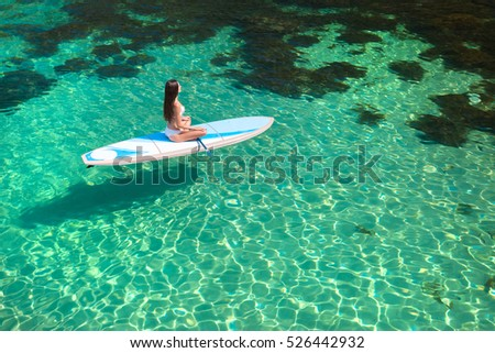 Young attractive woman meditating on the sup board in the sea. Girl in meditative pose on water.