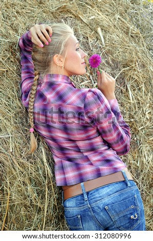 young attractive woman near the haystack in summer day - stock photo