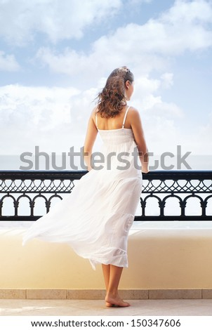 Young attractive woman on the balcony - stock photo
