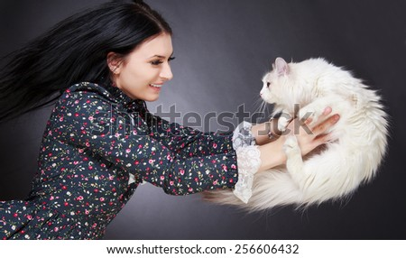Young attractive woman playing with a cat over grey background - stock photo