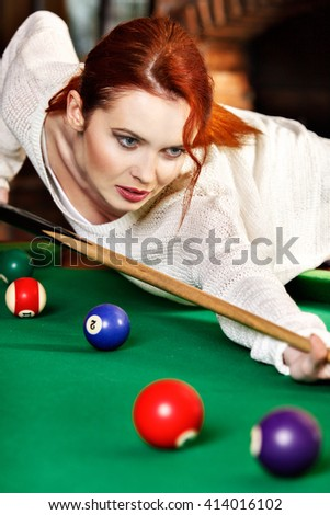 Young attractive woman plays the game of snooker pool table - stock photo