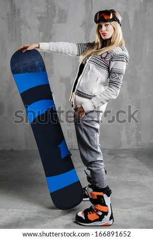 Young attractive woman posing in the studio against concrete wall with snowboard - stock photo