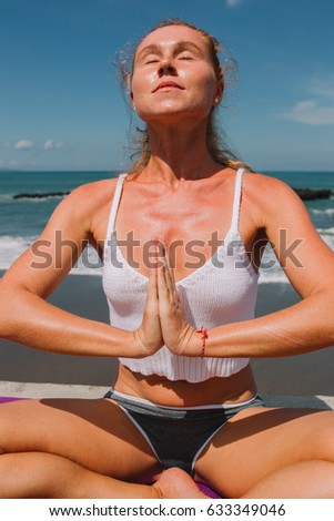 Young attractive woman practicing yoga with Namaste on the beach of Indian ocean, Indonesia, Bali