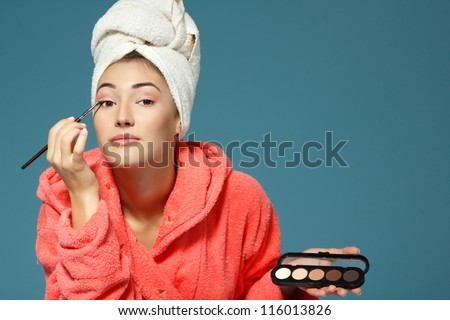 young attractive woman putting eye shadow with cosmetics brush over blue background, beauty treatment morning - stock photo